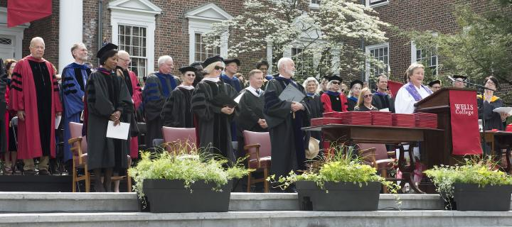 Wells faculty on stage at Commencement
