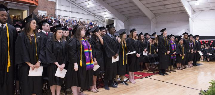 Seniors stand during the Commencement ceremony