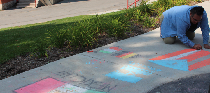 student making sidewalk art of flags of mexico, honduras, puerto rico and more