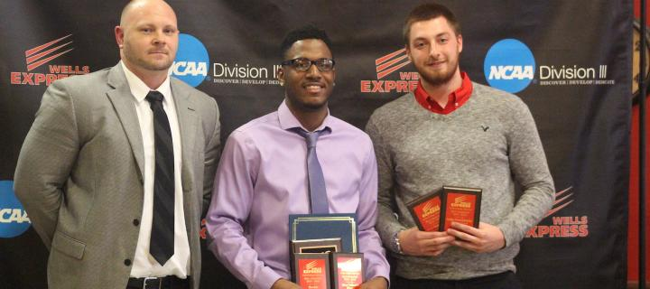 male student athletes with coach and awards