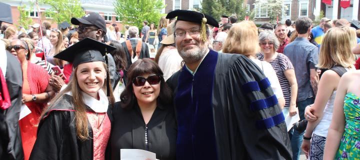 faculty posing with student after Commencement