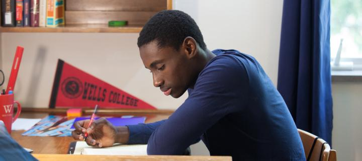 Wells College student in residence hall room studying