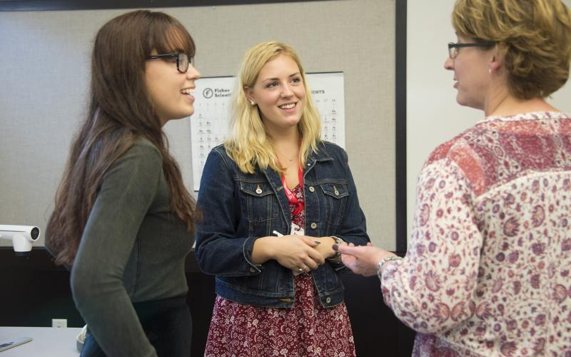 students speaking with the director of alumnae and alumni engagement
