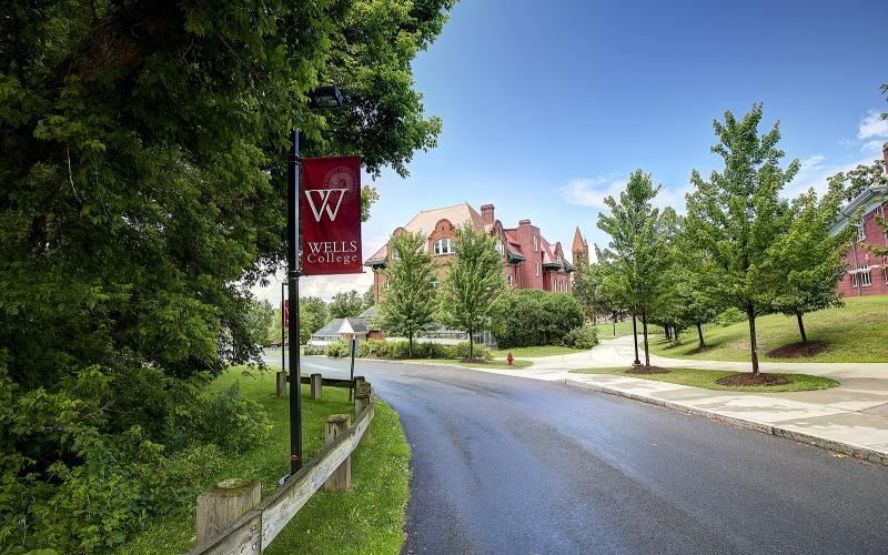image of campus roadway with wells banner