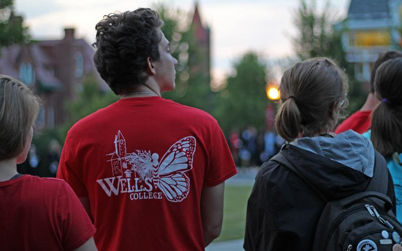 student wearing wells shirt with sunset in background