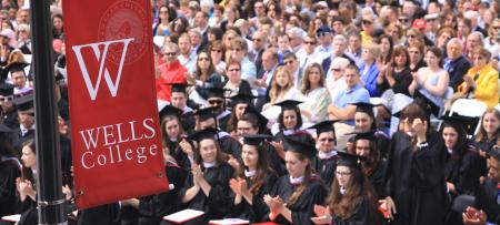 Wells College banner in front of seated graduates and families