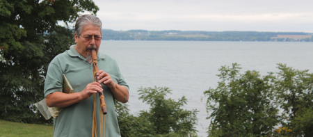 dan hill playing his flute with the lake in the background