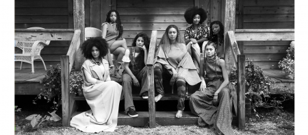 photo of women in various outfits sitting on the stairs of an old house