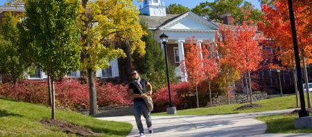 student on sidewalk with autumn trees