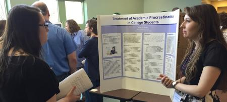 student discussing research with participants at the conference