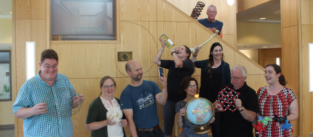 wells professors with props related to their fields - a globe, a spring, a model of a molecule, and more