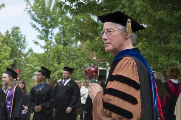 photo of professor with ceremonial mace at commencement
