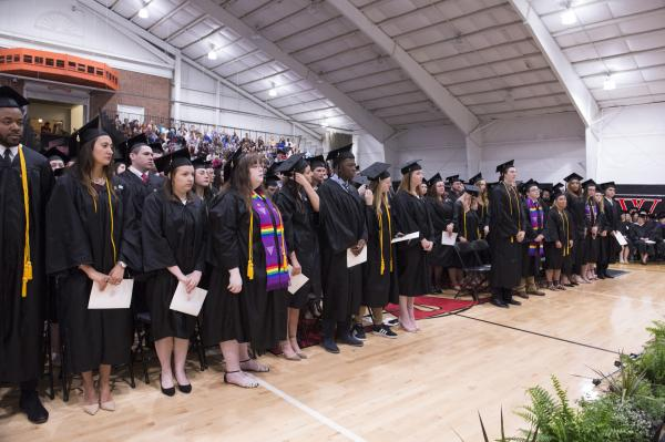 Graduates stand during the Commencement ceremony