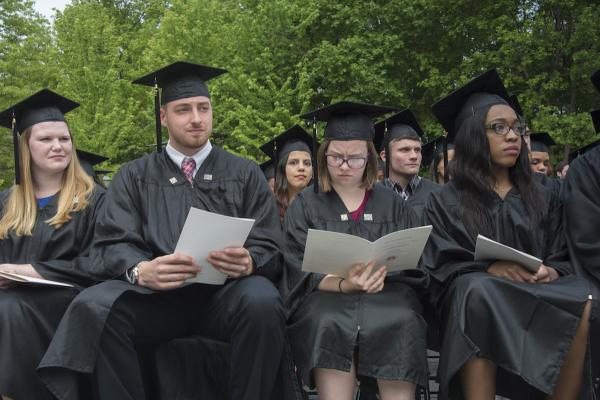 students in caps and gowns reading programs