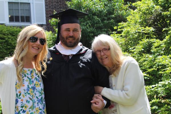 student in cap and gown with family