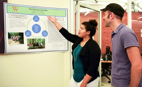 student and professor discussing internship poster