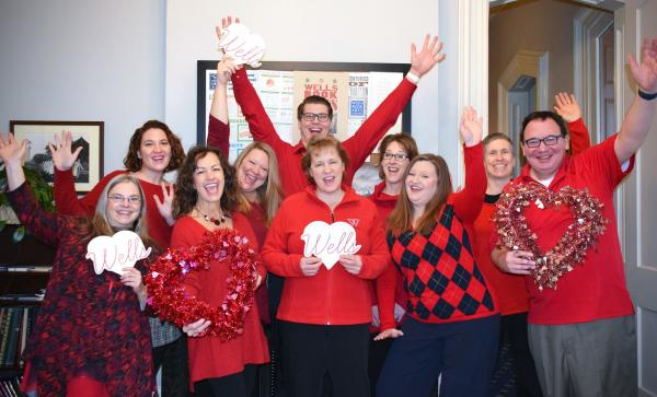 photo of advancement staff wearing red sweaters and celebrating