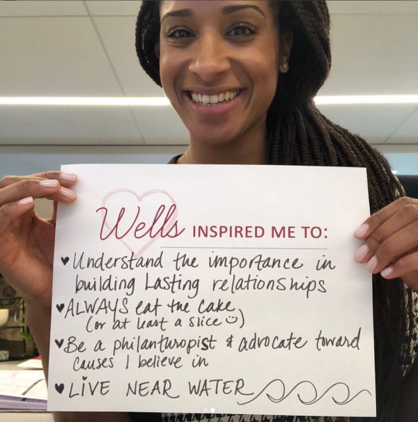 photo of alumna with sign saying wells inspired her to understand the importance of building lasting relationships and always live near water