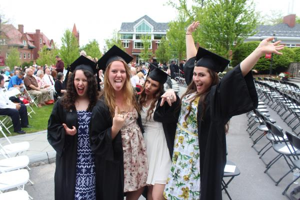 photo of four graduates in cap and gown looking excited
