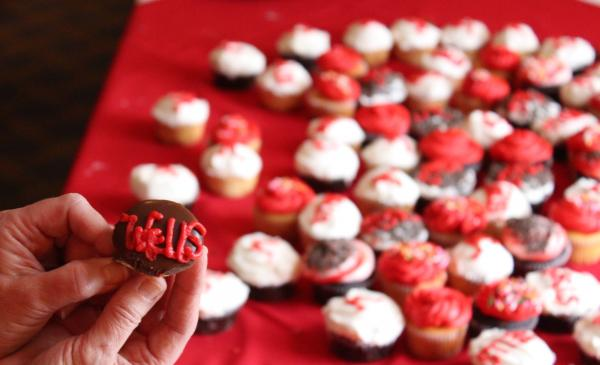 image of hands holding cupcake that says wells
