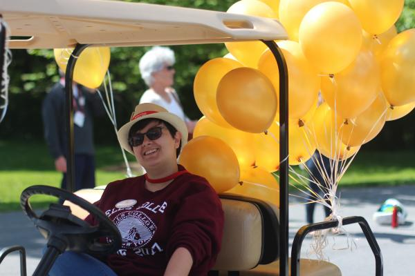 photo of student reunion worker with golf cart and balloons