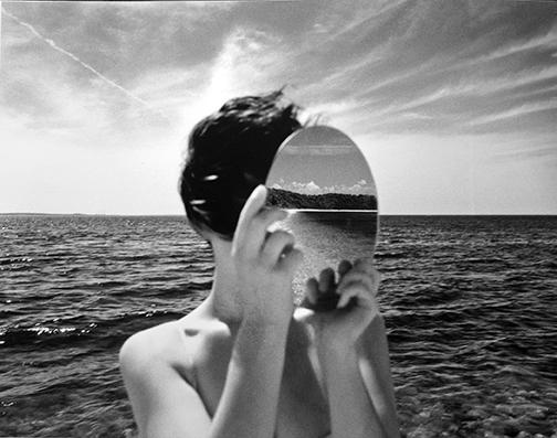 photo of woman holding mirror at the ocean by Julia Forrest