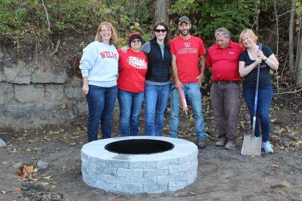 Alumni posing with Boathouse fire pit