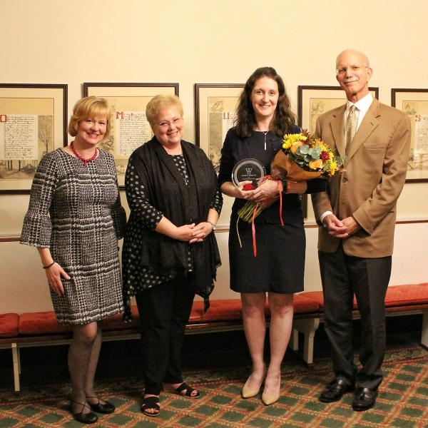 Christin Schaaf holding flowers and standing with President Gibralter and two others