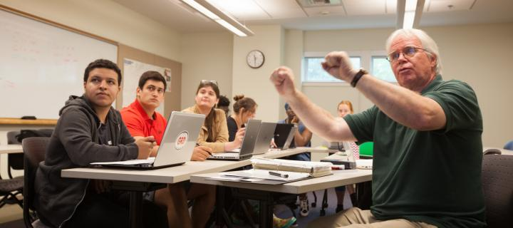 Professor Chris Bailey points to white board during class