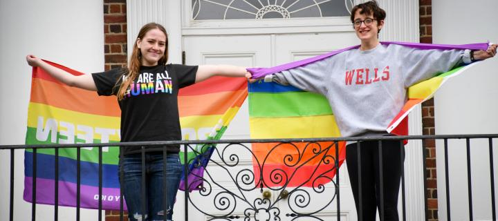 students holding rainbow flags outside Macmillan hall