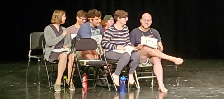 Group of actors sitting in chairs on stage, rehearsing