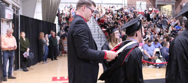 Matt Sleezer '14 hooding his brother, Adam Sleezer '18 at Commencement