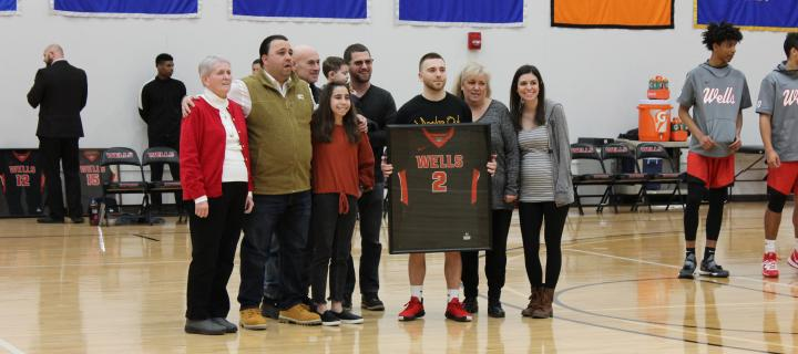 family poses for photos on mens' basketball senior day