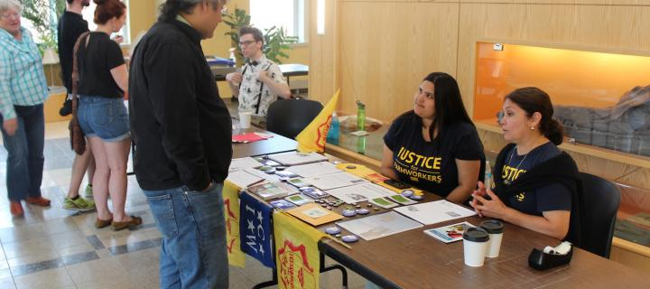 professor speaking with farmworker activists at information table
