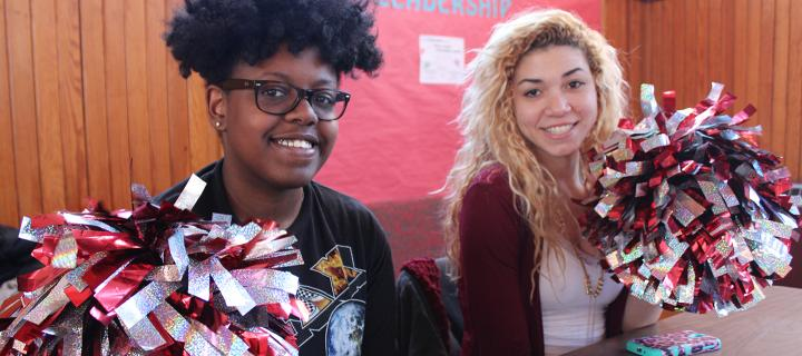 two students with pom poms at club fair