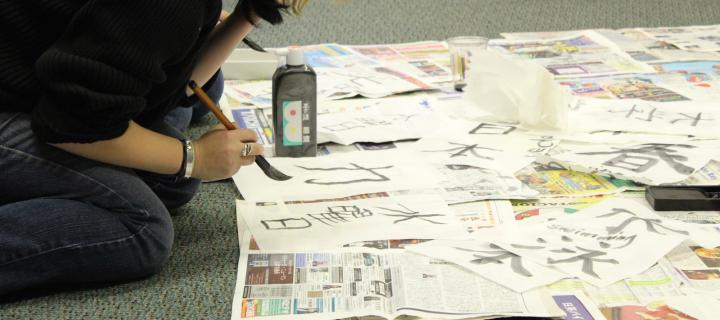 student with brush making calligraphy