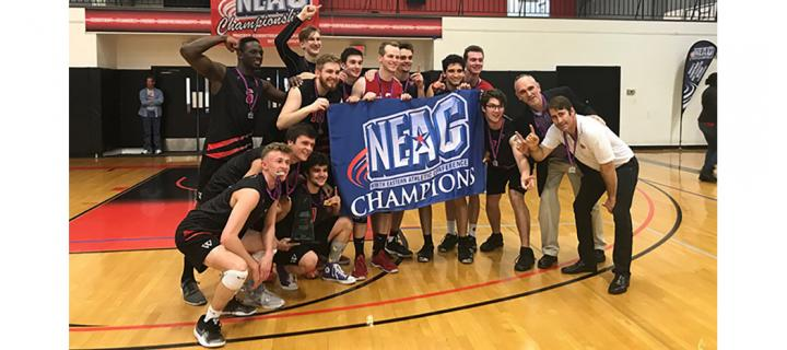 Men's volleyball team pose with NEAC championship banner