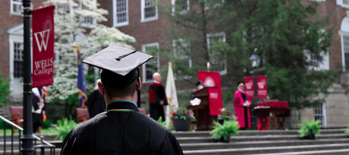 A student, seen from behind, wearing academic regalia and facing the stage