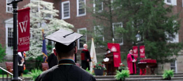 Student in graduation regalia as seen from behind, facing stage
