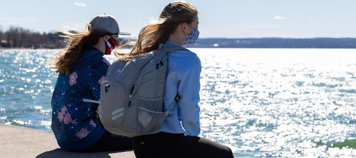 Two Wells students sit on boathouse dock, looking at Cayuga Lake