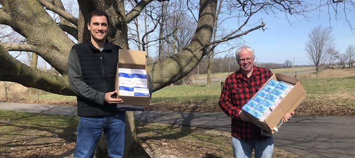 Zach VanNostrand and Christopher Bailey holding boxes of donated supplies