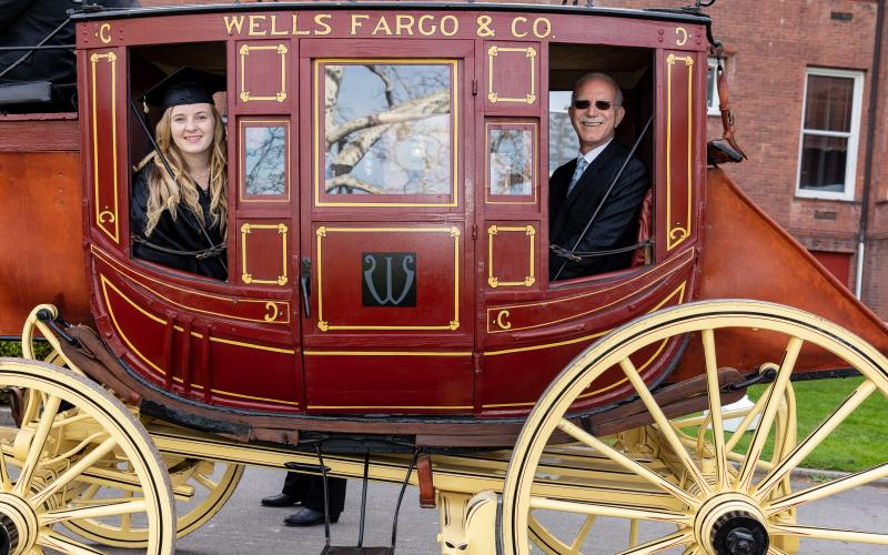 Carley Ryan and President Gibralter in the Wells Fargo Stagecoach during Commencement 2019