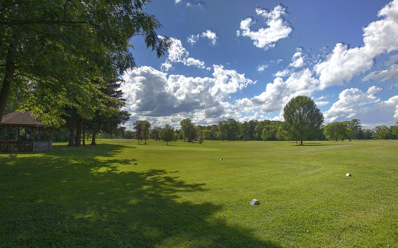 wide shot of golf course with beautiful clouds