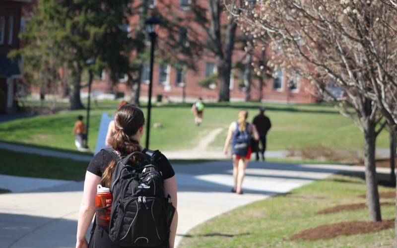 student with backpack walking on campus