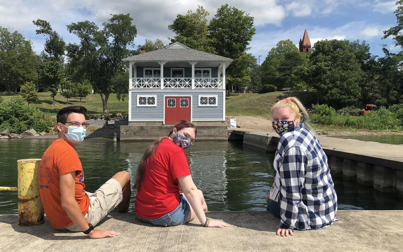 Wells students look toward camera with boathouse in background