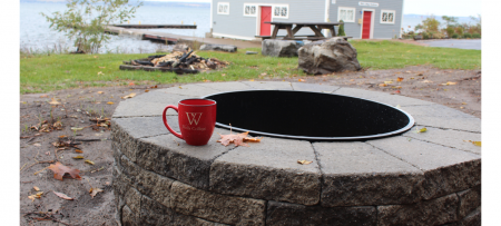 Wells mug sitting on the new fire pit with Cayuga Lake in the background