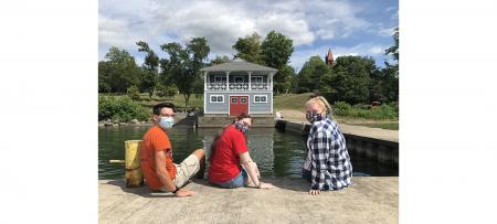 Three Wells College students sitting on dock, with boathouse behind them.