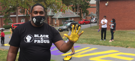 andre lynch waves with BLM paint project on the sidewalk behind him