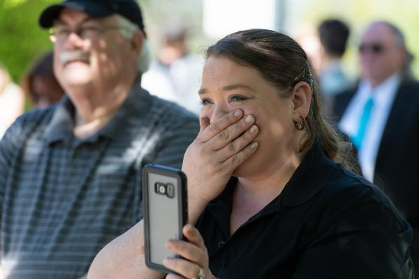 woman holding cell phone putting hand over mouth
