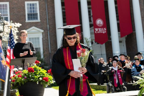 Graduate holding flowers descending the steps